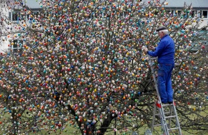 German pensioner Kraft decorates tree with Easter eggs in garden of his summerhouse in Saalfeld